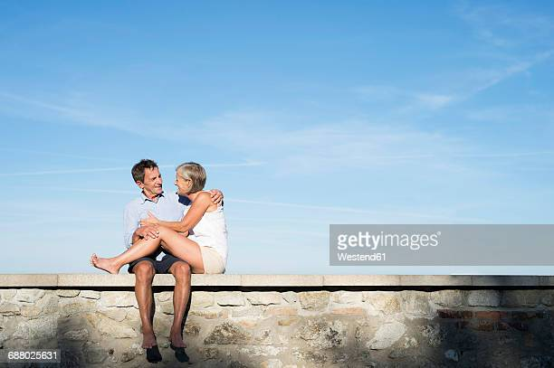 Senior couple sitting barefoot on a wall in front of sky