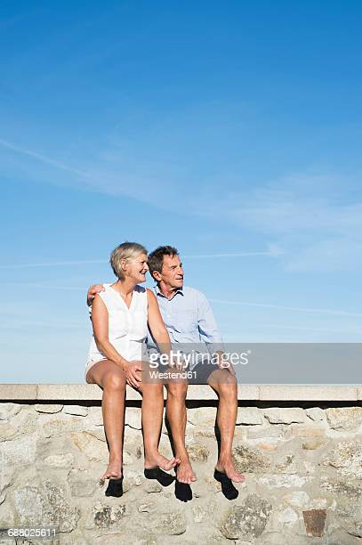 Senior couple sitting barefoot on a wall in front of sky watching something