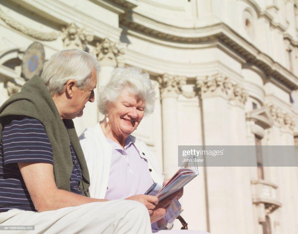 Senior couple sitting bench, reading book : Stock Photo