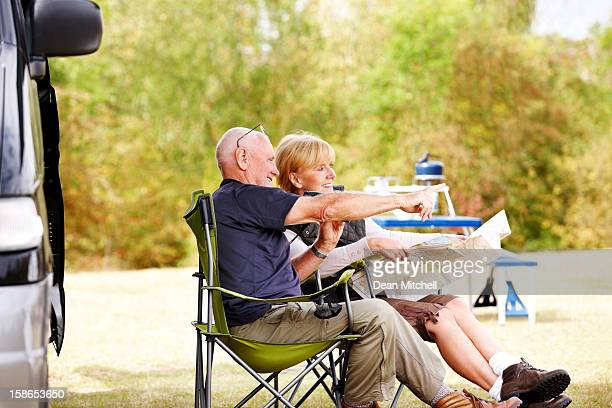 Senior couple sitting by camper van reading a map