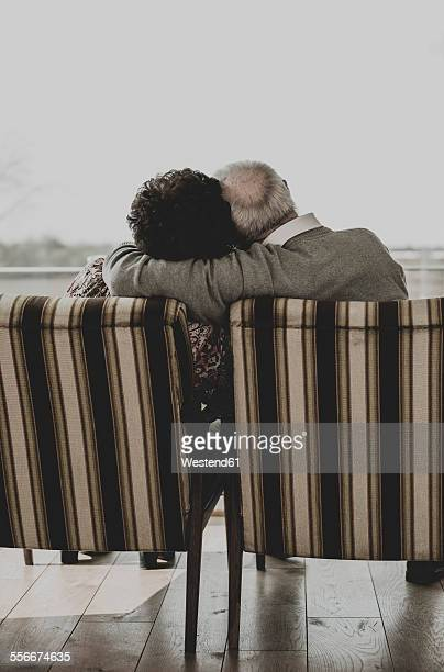 Senior couple sitting head to head in arm chairs looking through window