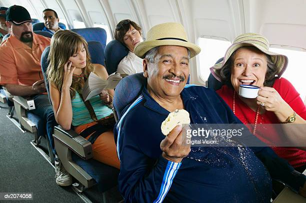 Senior Couple Sitting in an Aircraft Cabin Eating and Drinking and Passengers Behind