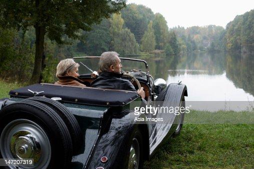 senior couple sitting in antique car lakeside