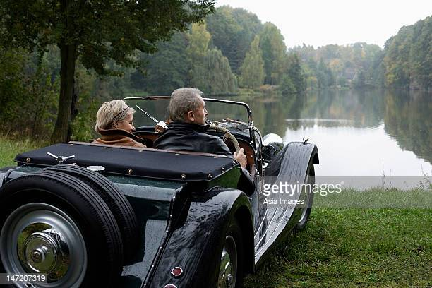 senior couple sitting in antique car lakeside