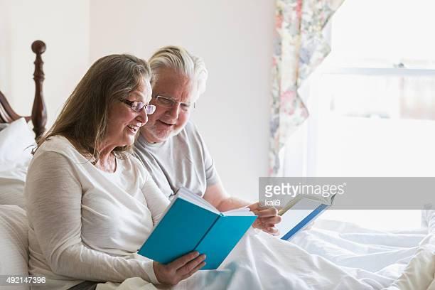 Senior couple assis dans leur lit des livres