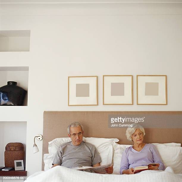 Senior couple sitting in bed, reading
