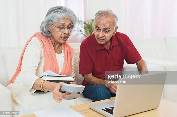 Senior couple sitting in front of a laptop checking bills