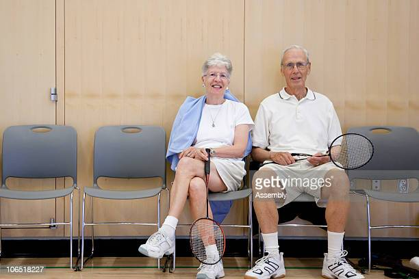 Senior couple sitting in gym with badminton gear