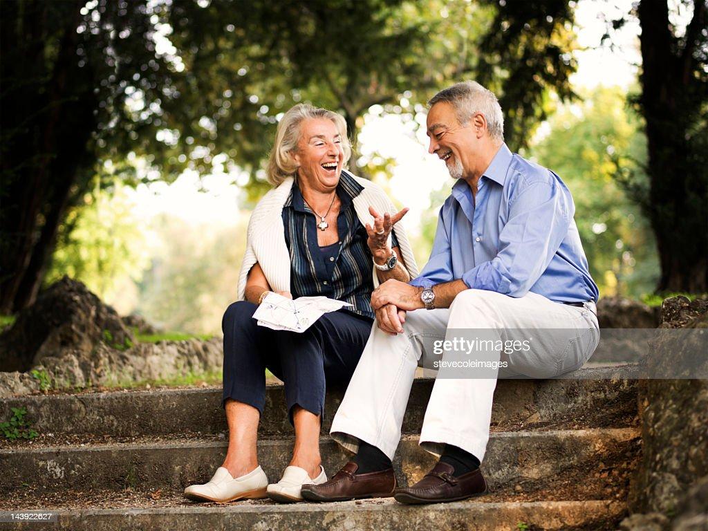 Senior Couple Sitting In Park Holding Map : Stock Photo