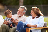 Senior couple sitting in the garden with their baby grandson, smiling at him, front view