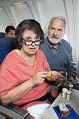 Senior Couple Sitting Inside a Plane, Woman Anxiously Taking Tranquilizers