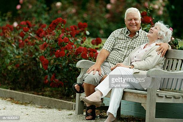 A Senior Couple Sitting on a Park Bench Next to Rose Bushes