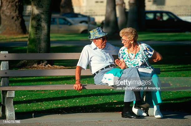 A senior couple sitting on a park bench talking Santa Monica CA