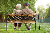 Rear view shot of a senior couple sitting on a wooden bench in the park