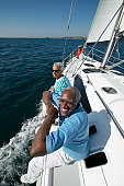 Senior Couple Sitting on a Yacht, Leaning on a Railing and Hanging Their Legs over the side