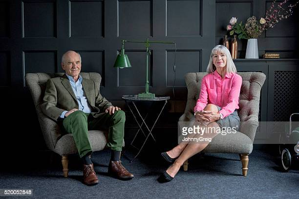 Senior couple sitting on armchairs in traditional living room