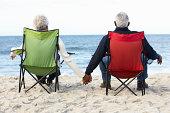 Senior Couple Sitting On Beach In Deckchairs
