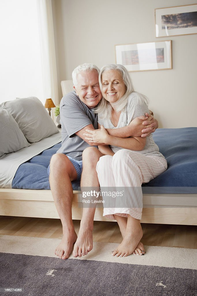 Senior couple sitting on bed in close embrace : Stock Photo