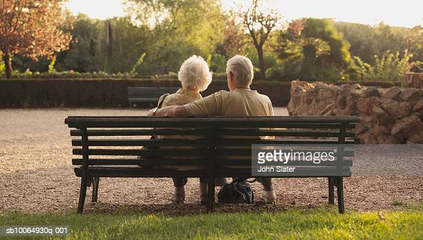 Senior couple sitting on bench in park, rear view