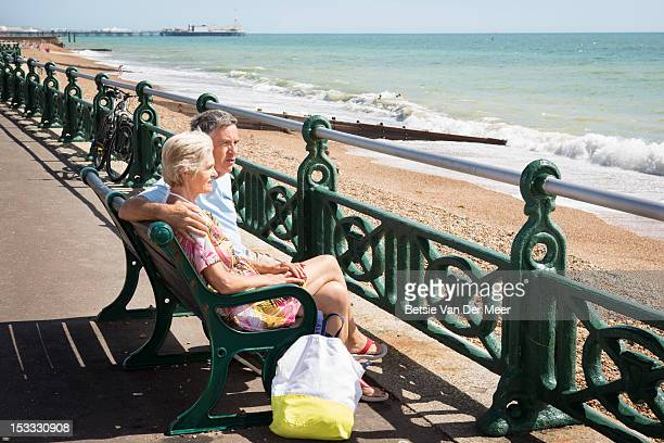 Senior couple sitting on bench looking at sea.
