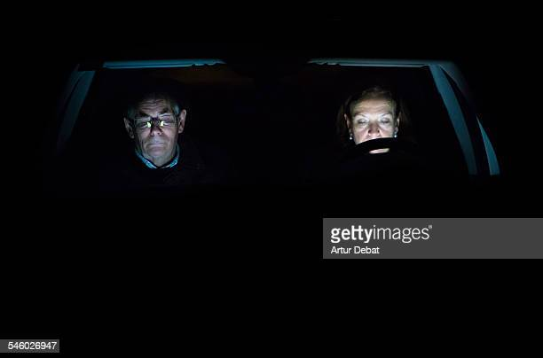 Senior couple sitting on car with screen light.