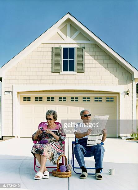 Senior Couple Sitting on Chairs on a Driveway in Front of a Garage, with the Woman Knitting and the Man Reading a Newspaper