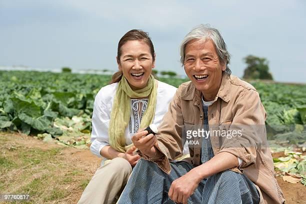 Senior couple sitting on field