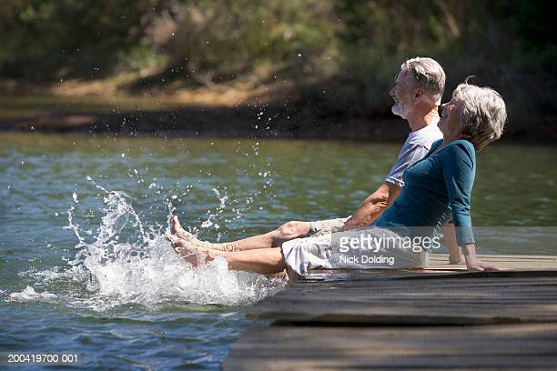 Senior couple sitting on lake jetty splashing feet in water, smiling