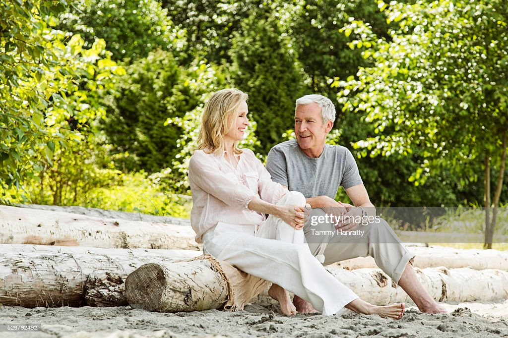 Senior couple sitting on logs : Stock Photo
