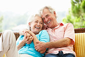 Senior Couple Sitting On Outdoor Seat Together Laughing