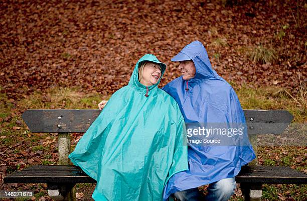 Senior couple sitting on park bench wearing waterproofs