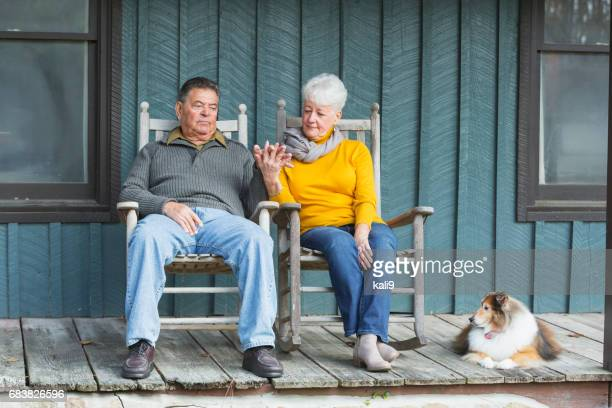 Senior couple sitting on porch, holding hands, with dog