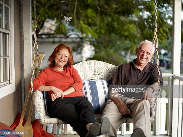 Senior couple sitting on porch swing, smiling, portrait