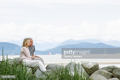Senior couple sitting on rocks : Stock Photo