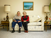Senior couple sitting on sofa, bird on man's shoulder, portrait