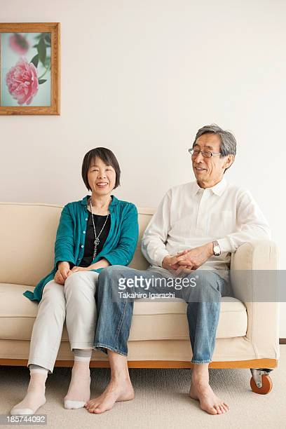 Senior couple sitting on sofa,  portrait