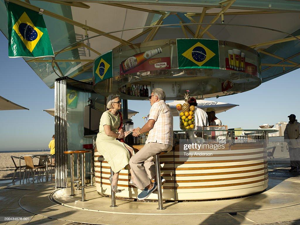 Senior couple sitting on stools at bar, outdoors : Stock Photo