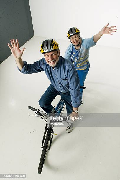 Senior couple sitting on tandem bicycle, posing in studio, portrait, elevated view