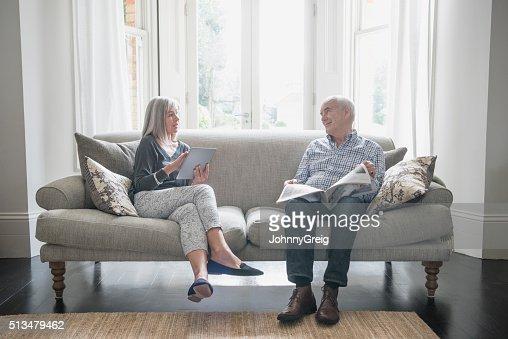Pareja mayor sentado en un sofá en casa, hablando