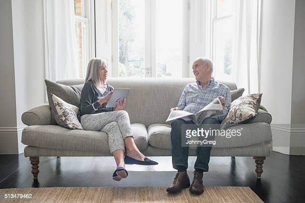 Senior couple assis sur le canapé à la maison, discuter