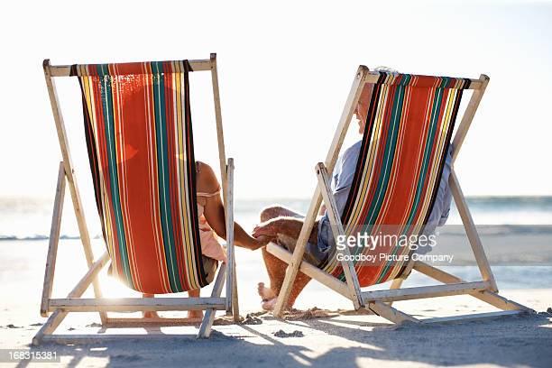Casal Idoso sentado no sol loungers