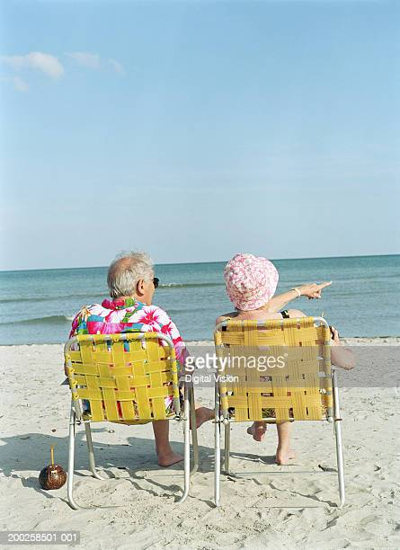 Senior couple sitting on yellow chairs on beach, rear view