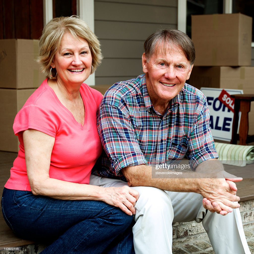 Senior Couple Sitting Outside House With For Sale Sign : Stock Photo