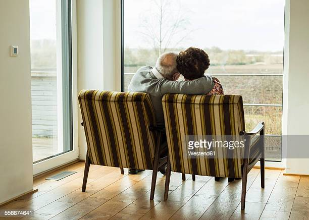Senior couple sitting side by side in arm chairs looking through window