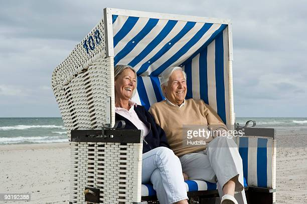 A senior couple sitting together in a hooded beach chair