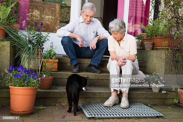 Senior couple sitting watching cat from back door step