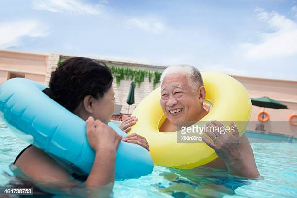 Senior couple smiling and relaxing in the pool with inflatable tubes