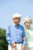 Senior couple smiling and walking, man holding a stick