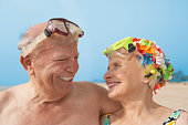 Senior couple smiling at each other at beach