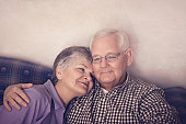 Senior couple snuggled on couch